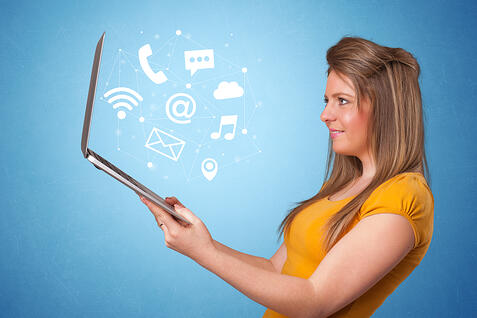 Woman holding laptop with online services symbols